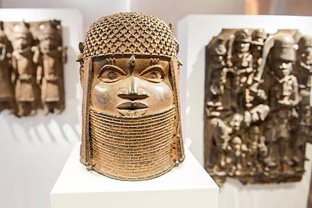 Drei Raubkunst-Bronzen aus dem Benin sind 2018 im Hamburger Museum für Kunst und Gewerbe in einer Vitrine ausgestellt. Foto: Daniel Bockwoldt/dpa