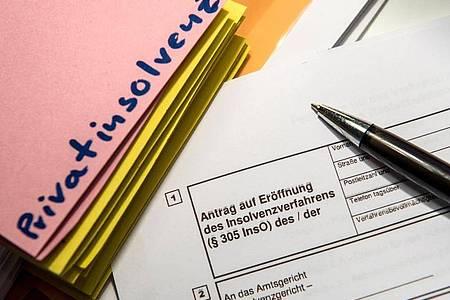 Das Wort «Privatinsolvenz» steht auf einem Trennblatt, während davor ein Antrag zur Eröfnung eines Insolvenzverfahrens liegt. Foto: Alexander Heinl/dpa