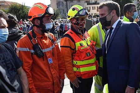 Der französische Präsident Emmanuel Macron (r) trifft Rettungskräfte während eines Besuchs in Tende im Südosten Frankreichs nach den schweren Unwettern. Foto: Christophe Simon/POOL AFP/AP/dpa