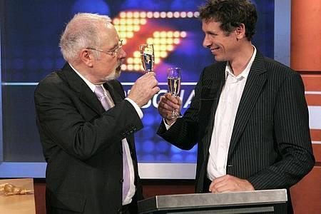 """Heribert Faßbender (l.) und Steffen Simon prosten sich im September 2006 mit einem Glas Sekt zu. """"Mister Sportschau"""" Heribert Faßbender wurde damals vom Westdeutschen Rundfunk (WDR) als Sportchef des Senders in den Ruhestand verabschiedet. Foto: picture alliance / dpa"""