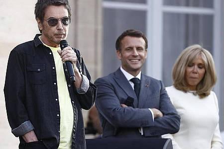Jean-Michel Jarre (l) spricht vor Staatschef Emmanuel Macron und seiner Frau Brigitte. Foto: Ian Langsdon/EPA POOL/AP/dpa