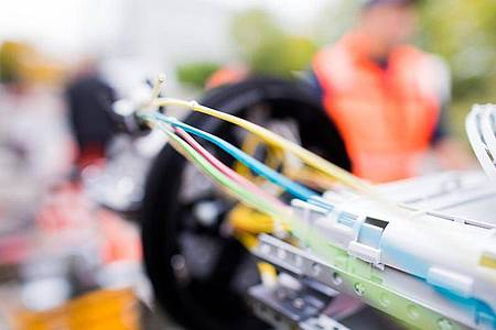 Ein Monteur verbindet Glasfaserkabel zu einer neuen Leitung. Foto: Rolf Vennenbernd/dpa