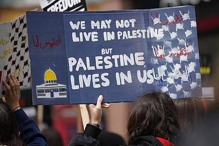 """Demo-Schild: """"Wir leben vielleicht nicht in Palästina, aber Palästina lebt in uns"""". Foto: Yui Mok/PA Wire/dpa"""