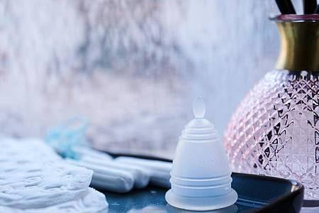 Eine Menstruationstasse, Slipeinlagen und Tampons verschiedener Hersteller liegen in einem Badezimmer. Foto: Annette Riedl/dpa/Archiv