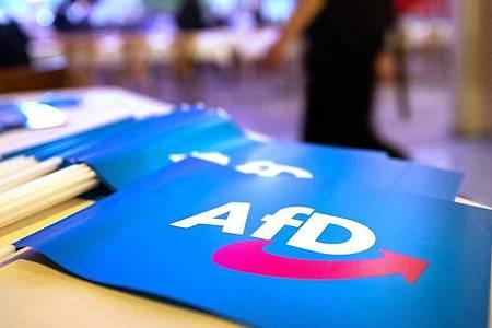 Fähnchen mit dem Logo der AfD liegen auf einem Tisch. Foto: Daniel Karmann/dpa
