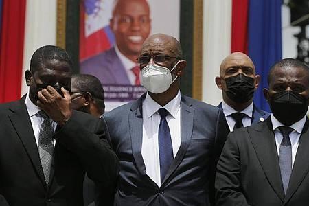 Arien Henry (M), designierter Premierminister von Haiti, und Interims-Regierungschef Claude Joseph (r) stehenvor einem Porträt des ermordeten haitianischen Präsidenten Jovenel Moise. Foto: Joseph Odelyn/AP/dpa