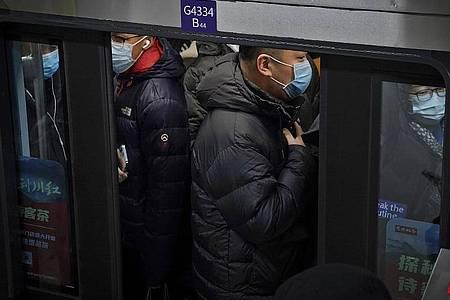 Pendler in Peking drängen sich in eine U-Bahn während der Hauptverkehrszeit. Foto: Andy Wong/AP/dpa