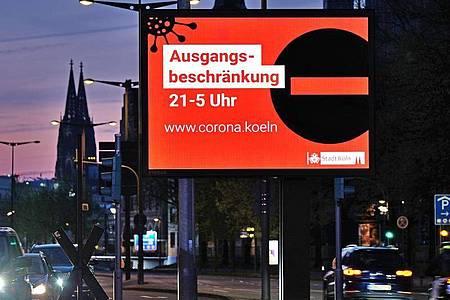 Eine Anzeigetafel in Köln weist Ende April auf die Ausgangsbeschränkung zwischen 21:00 und 05:00 Uhr hin. Foto: Oliver Berg/dpa