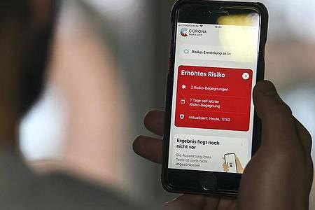 Auf einem Handy zeigt die «Corona Warn-App» ein erhöhtes Risiko an, welches darauf hinweist Kontakt mit einer infizierten Person gehabt zu haben. Foto: Kira Hofmann/dpa