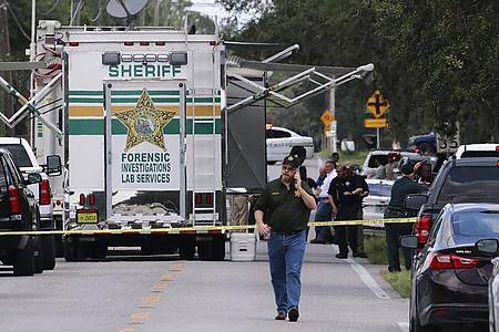 Kriminalbeamte im US-Bundesstaat Florida untersuchen nach einer Schießerei mit mehreren Toten den Tatort. Foto: Michael Wilson/The Lakeland Ledger via AP/dpa
