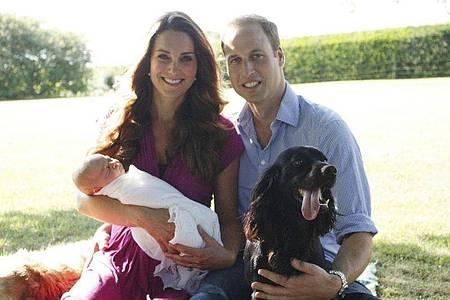 Prinz William und Herzogin Kate 2013 mit ihrem Sohn Prinz George umgeben von Retriever Tilly (l) und Cockerspaniel Lupo. Foto: Michael Middleton/PA Media/dpa