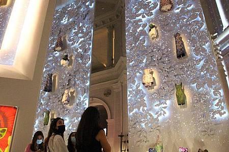 An einer hohen Wand hängen Kleidungsstücke und Accessoires von Christian Dior. Foto: Christina Horsten/dpa