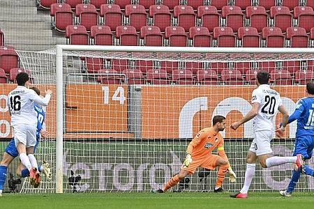 Augsburgs Mittelfeldspieler Ruben Vargas (l) erzielt den Treffer zum 1:0 - Hoffenheims Torwart Oliver Baumann (M) kann dem Ball nur hinterherschauen. Foto: Peter Kneffel/dpa
