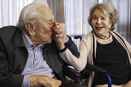 Kirk Douglas küsst die Hand seiner Frau Anne während einer Party zu seinem 100. Geburtstag. Foto: Reed Saxon/AP/dpa