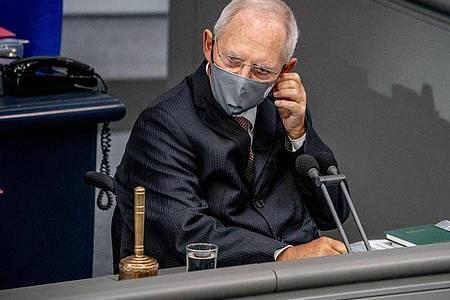 Wolfgang Schäuble (CDU), Bundestagspräsident, nimmt vor der Regierungsbefragung seine Maske ab. Foto: Michael Kappeler/dpa