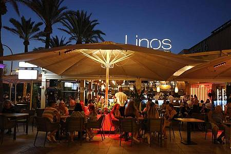 Menschen sitzen in einer Bar an der Strandpromenade von Palma. Foto: Clara Margais/dpa