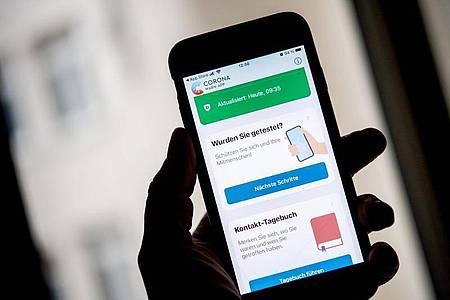 Die aktuelle Version 1.10 der Corona-Warn-App auf einem iPhone - das neuste Feature ist ein Kontakt-Tagebuch. Foto: Zacharie Scheurer/dpa-tmn