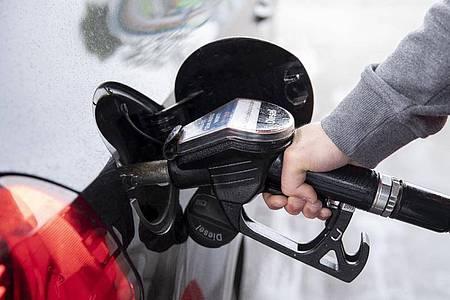 Ein Autofahrer steckt an einer Tankstelle einen Zapfhahn in die Tanköffnung seines Fahrzeugs. Für Kraftstoffe und Heizöl mussten Verbraucher zuletzt deutlich tiefer in die Tasche greifen als ein Jahr zuvor. Foto: Felix König/dpa