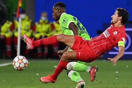 Wolfsburgs Ridle Baku (l) und Sevillas Jesus Navas kämpfen um den Ballbesitz. Foto: Swen Pförtner/dpa