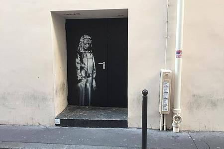 """Auf einer Tür beim Pariser Musikclub """"Bataclan"""" ist ein Wandbild zu sehen, das dem britischen Street-Art-Künstler Banksy zugerechnet wird. Foto: Sebastian Kunigkeit/dpa"""