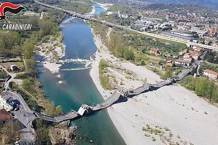 Die von der Polizei zur Verfügung gestellte Luftaufnahme zeigt die eingestürzte Brücke über einem Fluss. Foto: Carabinieri/dpa