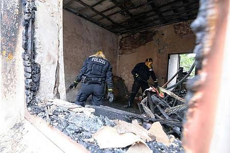 Zwei Brandermittler der Polizei im Einsatz. Foto: Jonas Walzberg/dpa