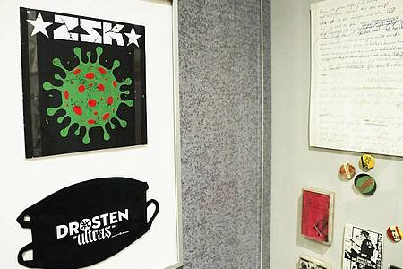 """Die Single """"Ich habe Besseres zu tun"""" über den Virologen Drosten und eine Maske mit der Aufschrift """"Drosten Ultras"""" der Punkband ZSK in Bonn. Foto: Oliver Berg/dpa"""