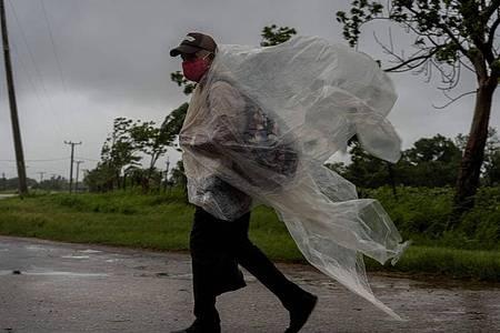 Ein Mann geht auf einer Straße nach Batabano in der kubanischen Provinz Mayabeque. Er versucht sich mit Plastikplanen gegen den von Hurrikan Ida verursachten Regen zu schützen. Foto: Ramon Espinosa/AP/dpa
