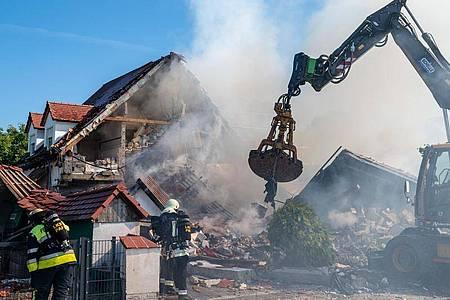 Ein Bagger räumt Teile des eingestürzten Hauses weg. Foto: Armin Weigel/dpa