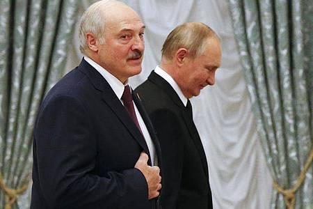 Alexander Lukaschenko (l), Präsident von Belarus, und Wladimir Putin, Präsident von Russland, gehen während einer gemeinsamen Pressekonferenz im Kreml durch den Saal. Foto: Shamil Zhumatov/Pool Reuters/AP/dpa