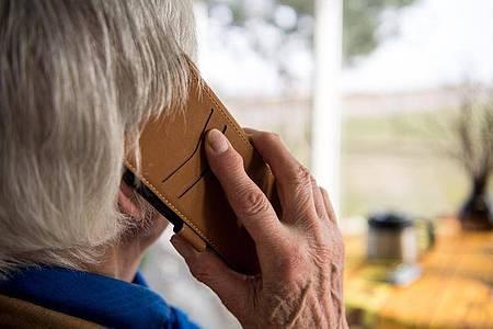 Seniorin am Telefon:Neben dem materiellen Schaden haben Anrufe für die Opfer auch häufig psychische Folgen. Foto: Sebastian Gollnow/dpa
