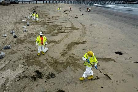 Arbeiter in Schutzanzügen reinigen den Strand nach einem Ölaustritt in Newport Beach, Kalifornien. Foto: Ringo H.W. Chiu/AP/dpa