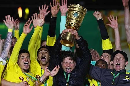 BVB-Coach Edin Terzic streckt den DFB-Pokal in den Berliner Nachthimmel. Foto: Martin Rose/Getty-Pool/dpa