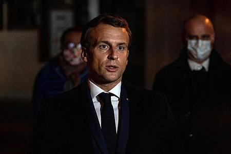 Emmanuel Macron, Präsident von Frankreich, spricht in der Nähe des Tatorts. Foto: Abdulmonam Eassa/POOL AFP/AP/dpa