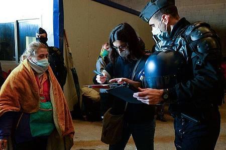 Polizisten notieren die Personalien von Jugendlichen nach dem Abbruch einer Party in einem in der Nähe gelegenen Hangar etwa 40 km südlich von Rennes. Foto: Jean-Francois Monier/AFP/dpa