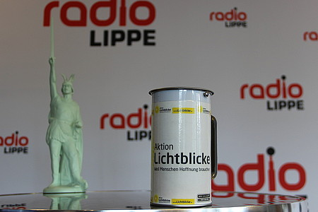 Spendendose für die Aktion Lichtblicke mit einer Hermann-Statue im Hintergrund