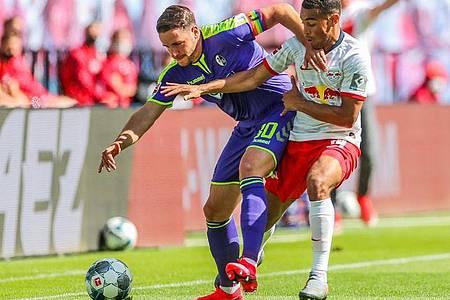 Der Freiburger Christian Günter (l) schirmt den Ball gegen Tyler Adams ab. Foto: Jan Woitas/dpa-Zentralbild/dpa