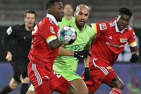 Unions Sheraldo Becker (l-r), Wolfsburgs John Brooks und Unions Taiwo Awoniyi kämpfen um den Ball. Foto: John Macdougall/AFP-Pool/dpa