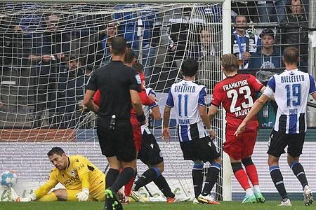 Bielefelds Torwart Stefan Ortega (l) kassiert den Gegentreffer zum 0:1 durch Frankfurts Jens Petter Hauge (2.v.r). Foto: Friso Gentsch/dpa