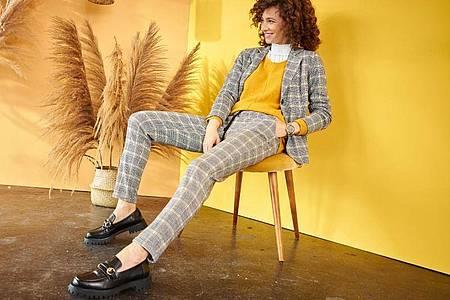 Bequem und doch schick: Die Hose hat wie eine Jogginghose einen Gummizug, getragen zum Blazer - ein Beispiel des aktuellen Trends von Aniston by Baur (Jersey-Blazer ca. 60 Euro, Hose ca. 50 Euro, gelber Pullover ca. 30 Euro). Foto: Baur/dpa-tmn