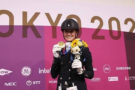 Dressurreiterin Jessica von Bredow-Werndl präsentiert ihre Goldmedaille. Foto: Friso Gentsch/dpa
