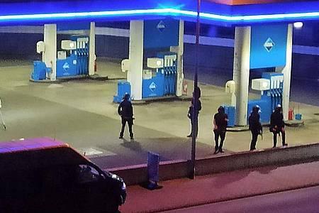 Polizisten sichern die Tankstelle, an der ein Angestellter von einem bewaffneten Mann erschossen wurden. Foto: Christian Schulz/Foto Hosser/dpa