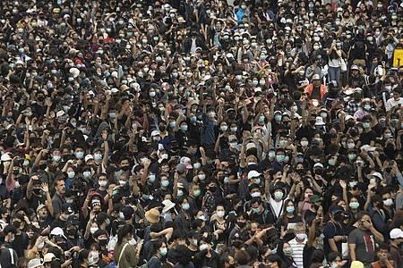 Pro-demokratische Demonstranten zeigen bei einem Protest auf dem Hauptbahnhof den Dreifingergruß als Symbol des Widerstands. Foto: Sakchai Lalit/AP/dpa