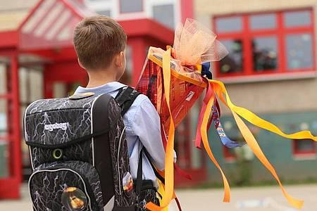 Ein Erstklässler wird mit seiner Schultüte in Sachsen-Anhalt eingeschult. Der Rechtsanspruch auf Ganztag in der Grundschule ist beschlossene Sache. Foto: Matthias Bein/dpa-Zentralbild/ZB