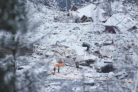 Rettungsmannschaften sind nach einem Erdrutsch zwischen zerstörten Gebäuden im Einsatz. Foto: Tor Erik Schroeder/ntb/AP/dpa