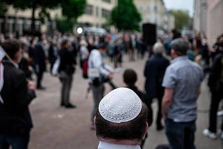Menschen stehen bei einer Solidaritätskundgebung inGelsenkirchen auf dem Platz vor der Synagoge. Dabei trägt ein Mann eine Kippa. Foto: Fabian Strauch/dpa