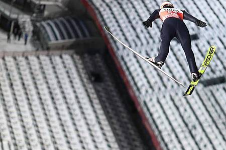 Schaffte es im ersten Durchgang auf 127 Meter: Karl Geiger schwebt vor der leeren Tribüne in Oberstdorf. Foto: Daniel Karmann/dpa