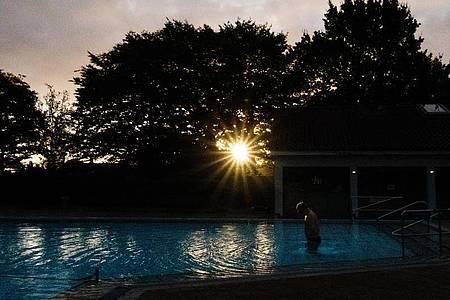Ein Badegast steigt am frühen Morgen bei Sonnenaufgang ins Schwimmbecken im Freibad Großburgwedel bei Hannover. Foto: Demy Becker/dpa