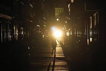 Eine Frau geht im Scheinwerferlicht eines patrouillierenden Polizeiwagens über die Bourbon Street in New Orleans. Foto: Eric Gay/AP/dpa