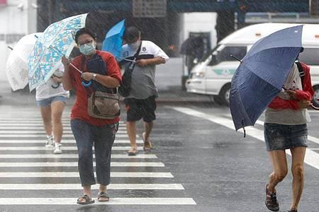 Menschen mit Regenschirmen kämpfen in Keelung gegen das Unwetter. Foto: Daniel Ceng Shou-Yi/ZUMA/dpa